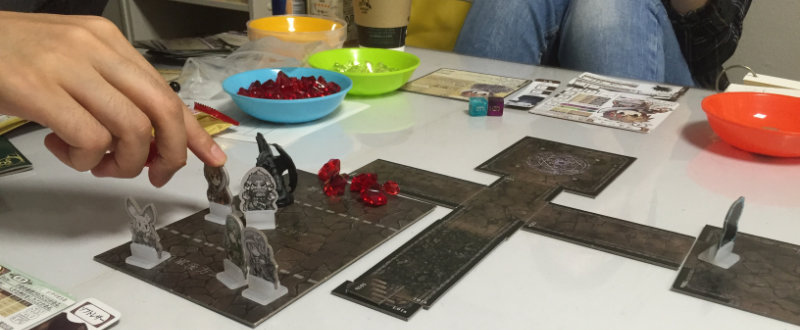 The battle map (left) and dungeon tiles (right). Three characters are in the player rear and two characters are in melee with a monster. The plastic miniature is not part of the starter set. The red health counters on the battle map are the enemy's health.