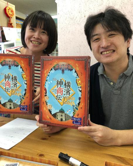 Designer Hisashi Hayashi and illustrator Ryoko Hayashi hold up their board game Yokohama