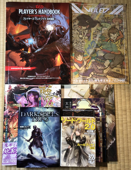 A variety of Japanese TRPGs stacked to show relative sizes. The only hardcover is the D&D 5e Player's Handbook.